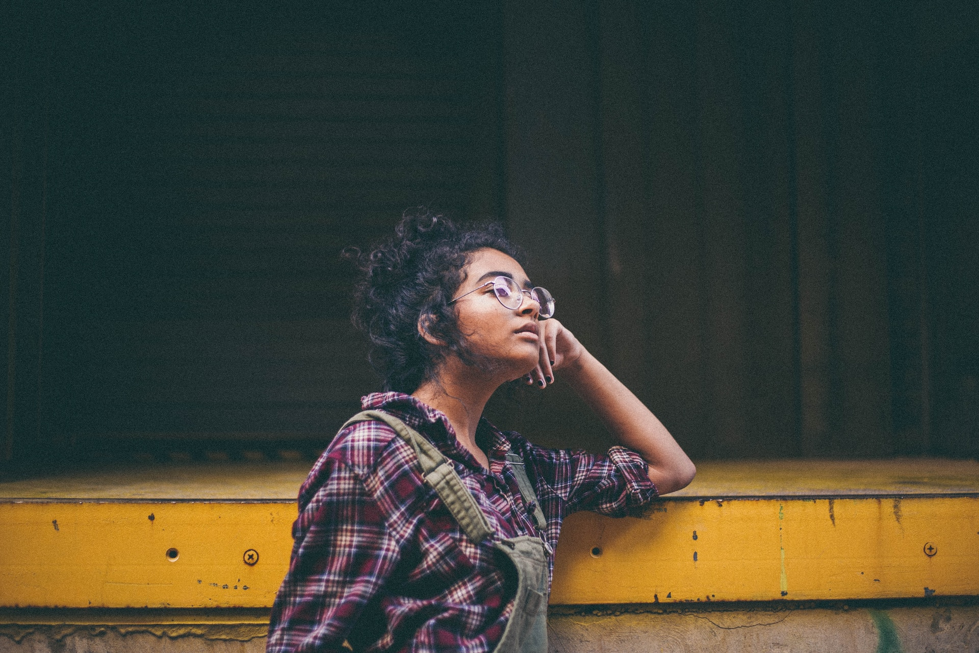 woman leaning on yellow surface