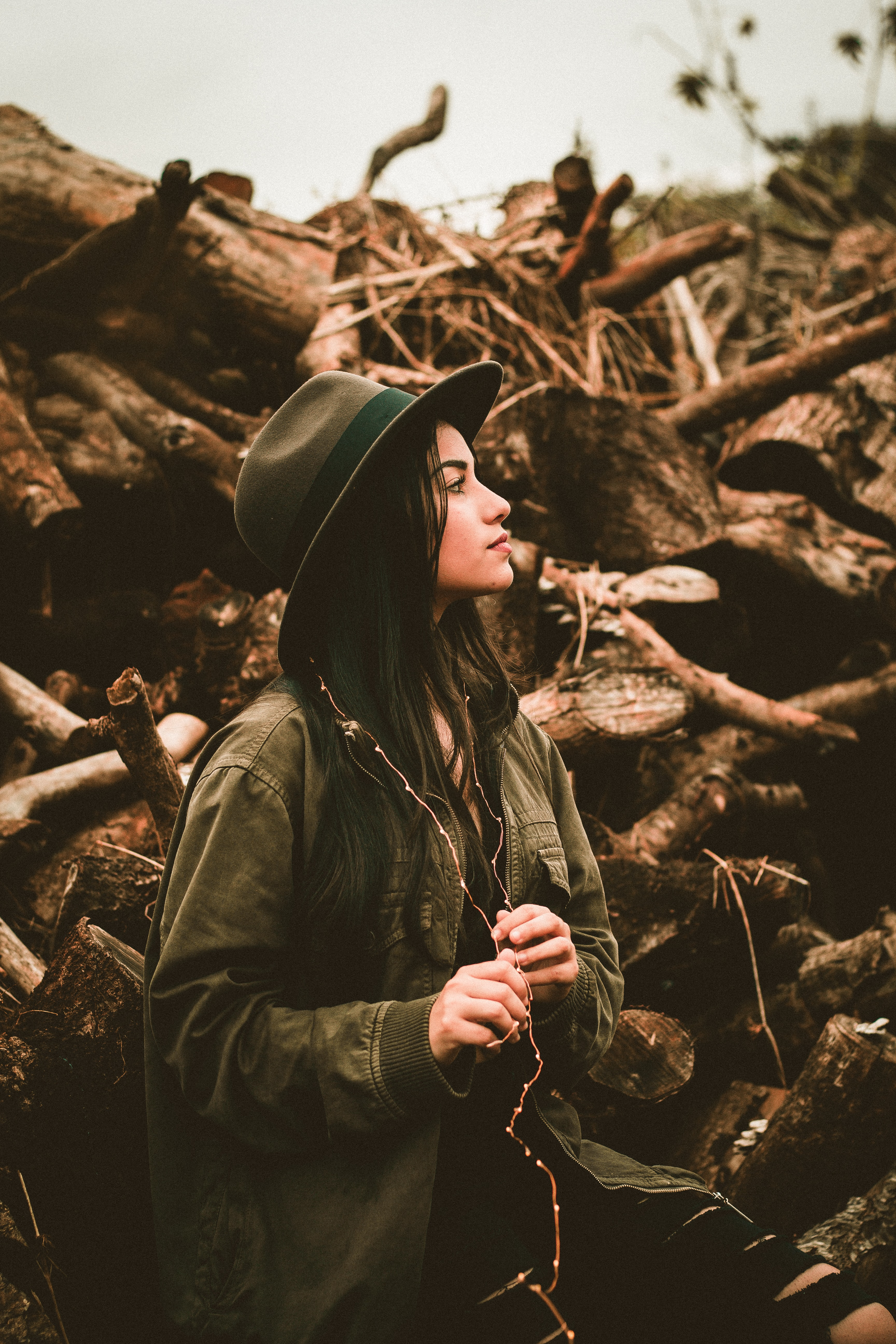 woman wearing bomber jacket and hat side viewing in front of wood logs