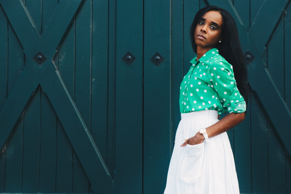 woman in white skirt and green dress shirt hand on pocket standing at the front of green door