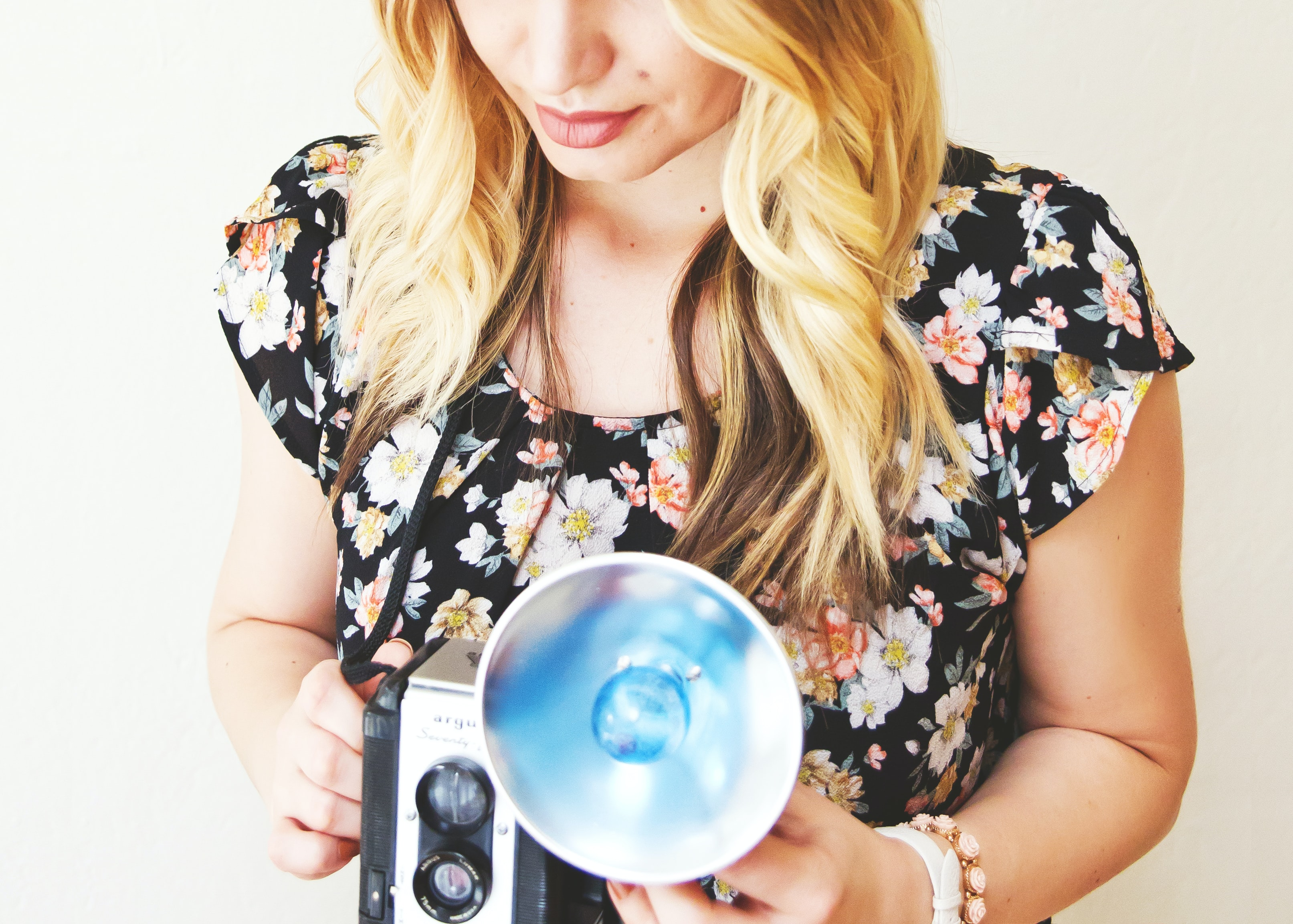 A blonde woman wearing a floral top taking a photo with a vintage camera