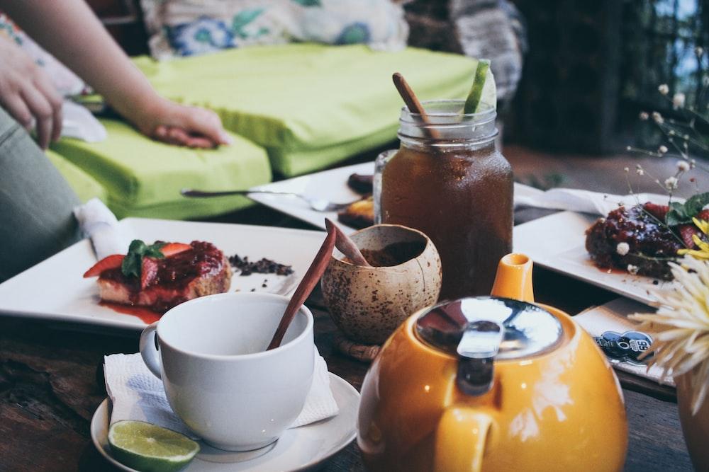 white ceramic mug beside orange ceramic teapot