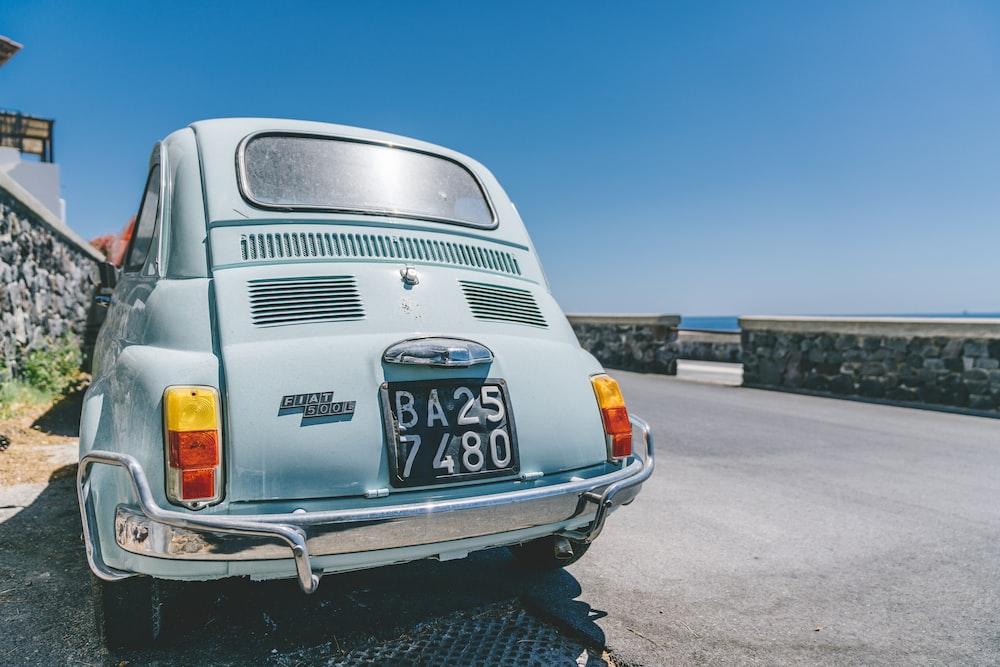 gray Volkswagen Beetle on gray concrete road