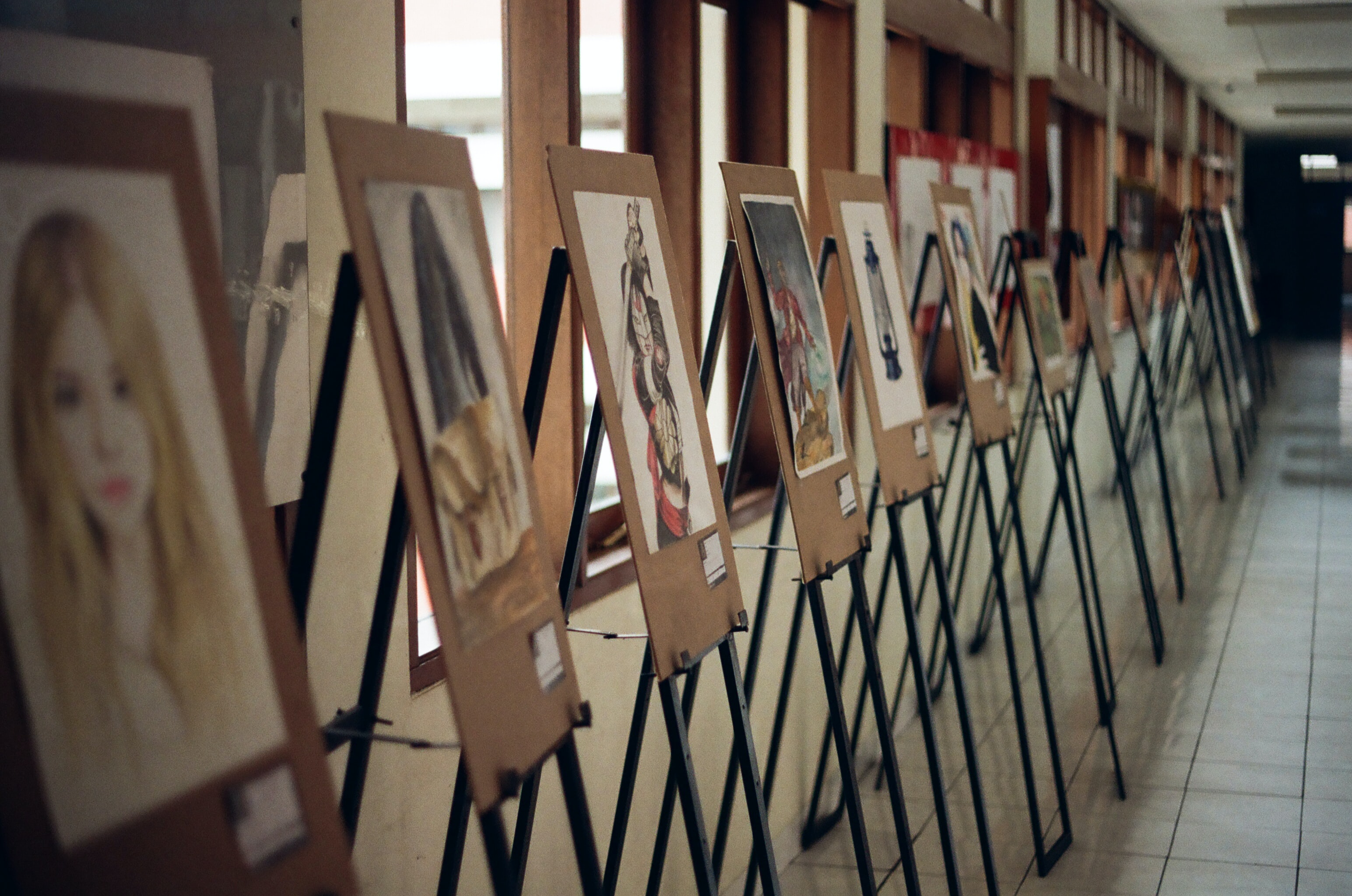 Easels holding up artwork of people and fictional characters in a long hallway