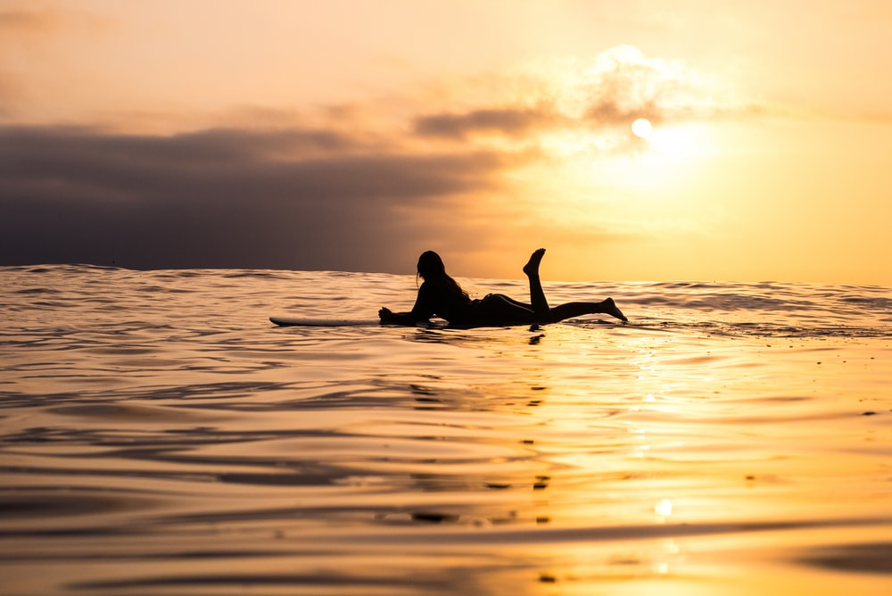 silhouette of woman lying on surfboard at the sea