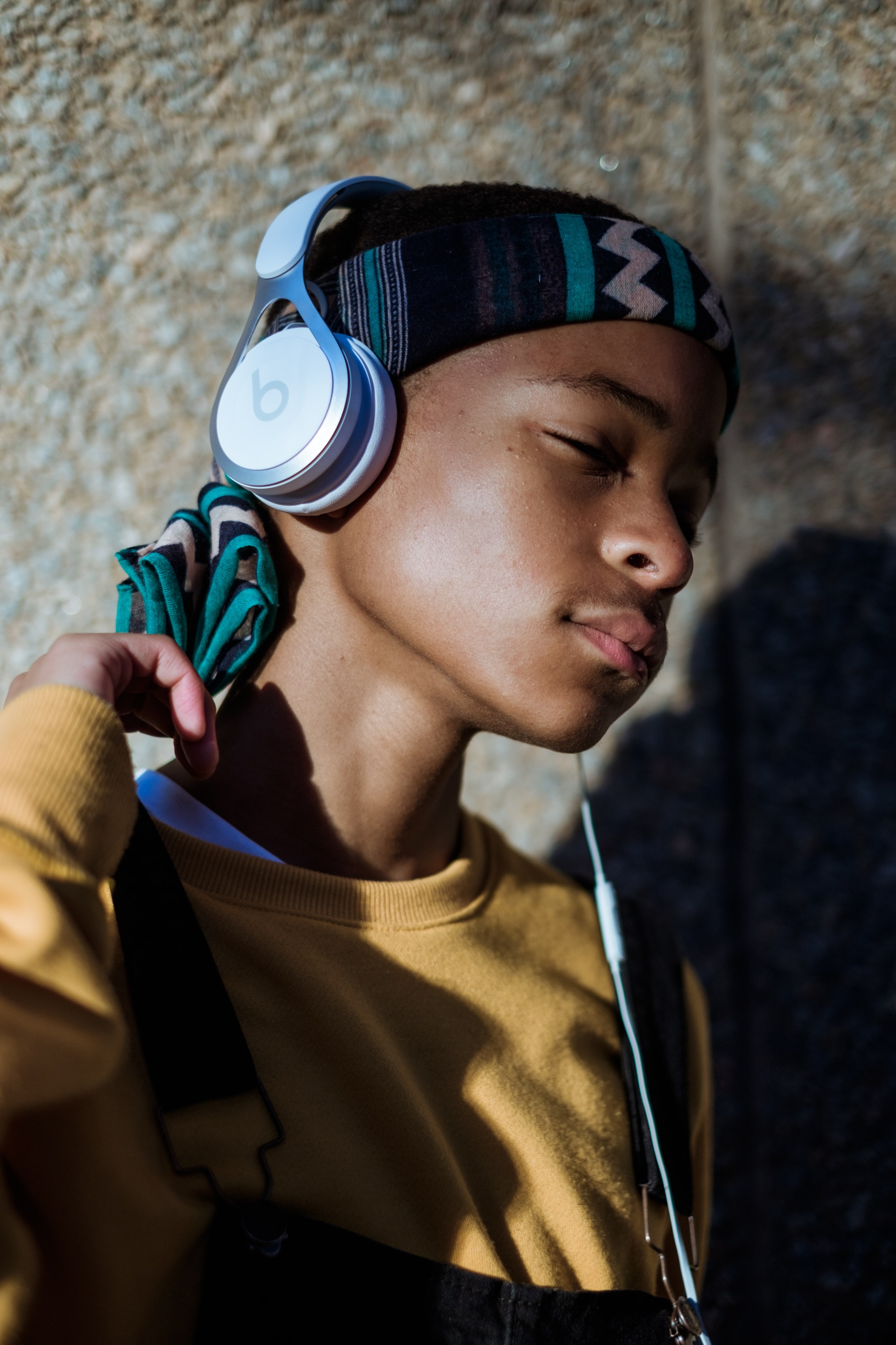 A person in a headwrap listens to music on white Beats by Dre headphones