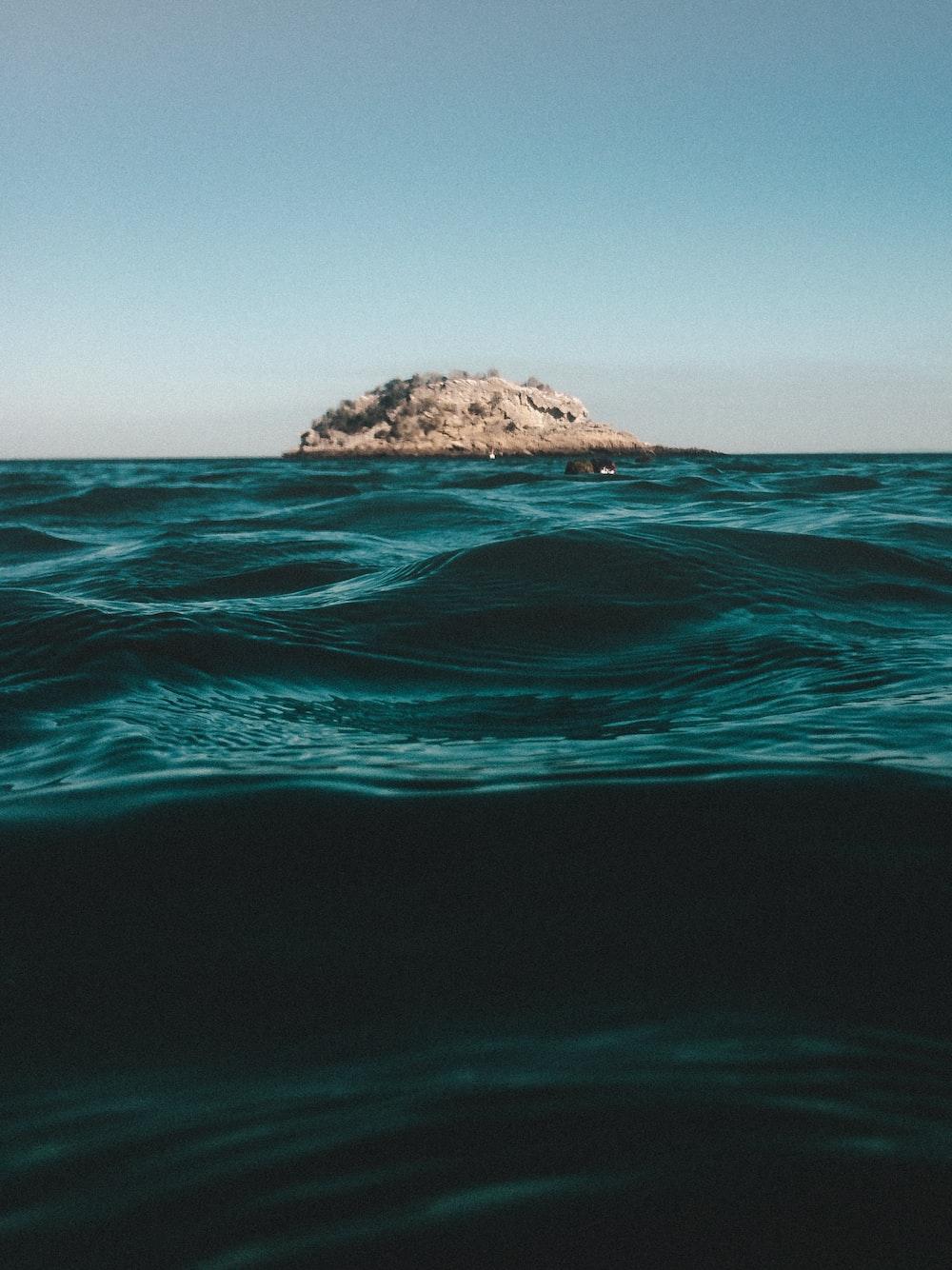 islet on ocean during daytim