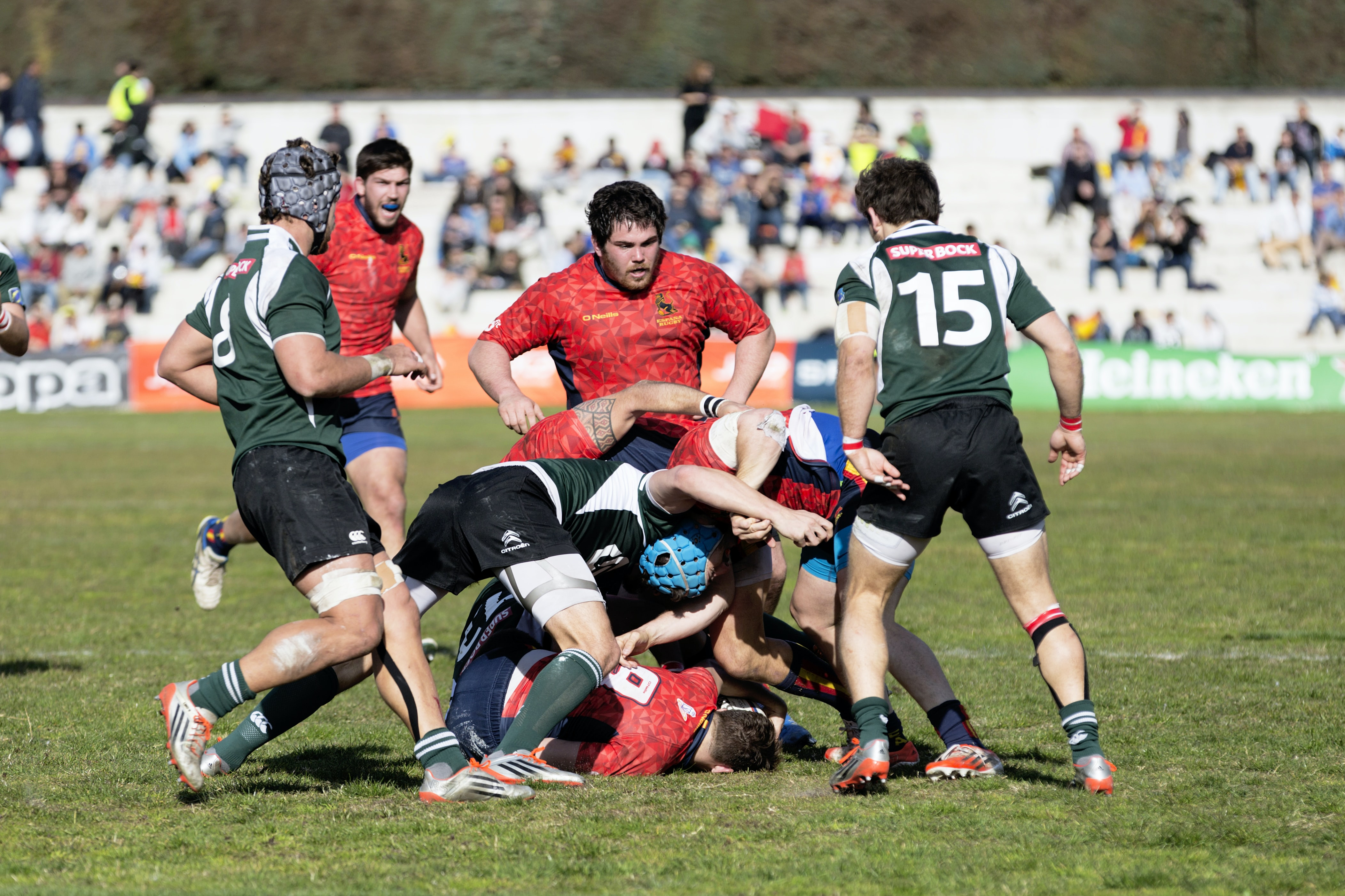 Rugby players in green and red jerseys on playing field with audience