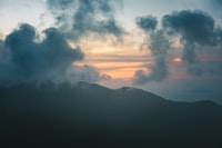 silhouette of mountain under cumulus clouds