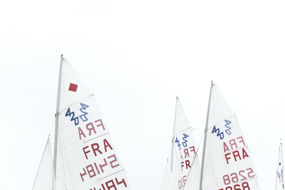 white and red sailboat sails