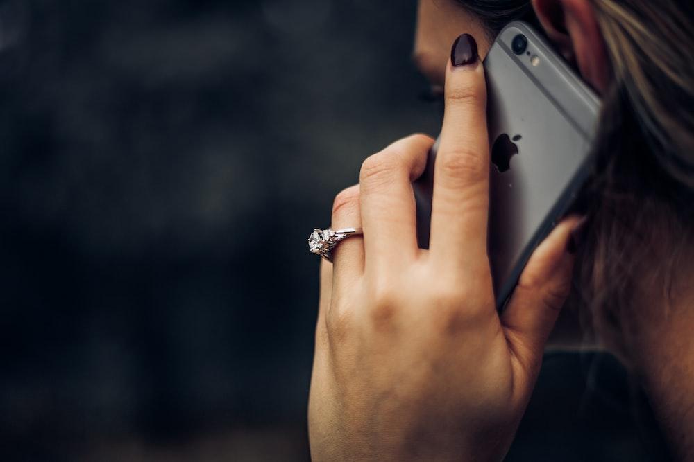 Woman wearing a diamond wedding ring talking on an iPhone
