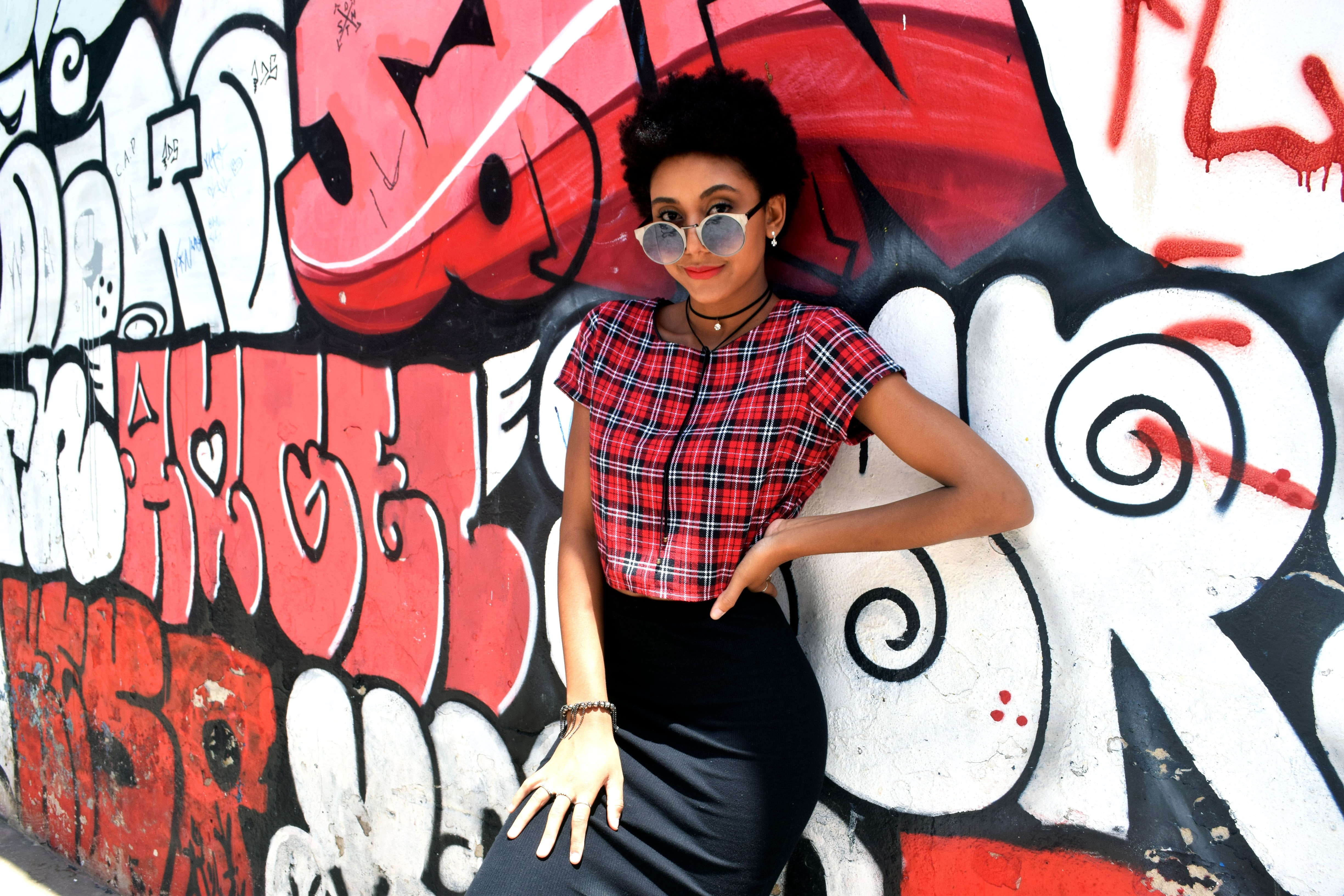 A woman in a plaid shirt leans against a black, red, and white graffitied wall