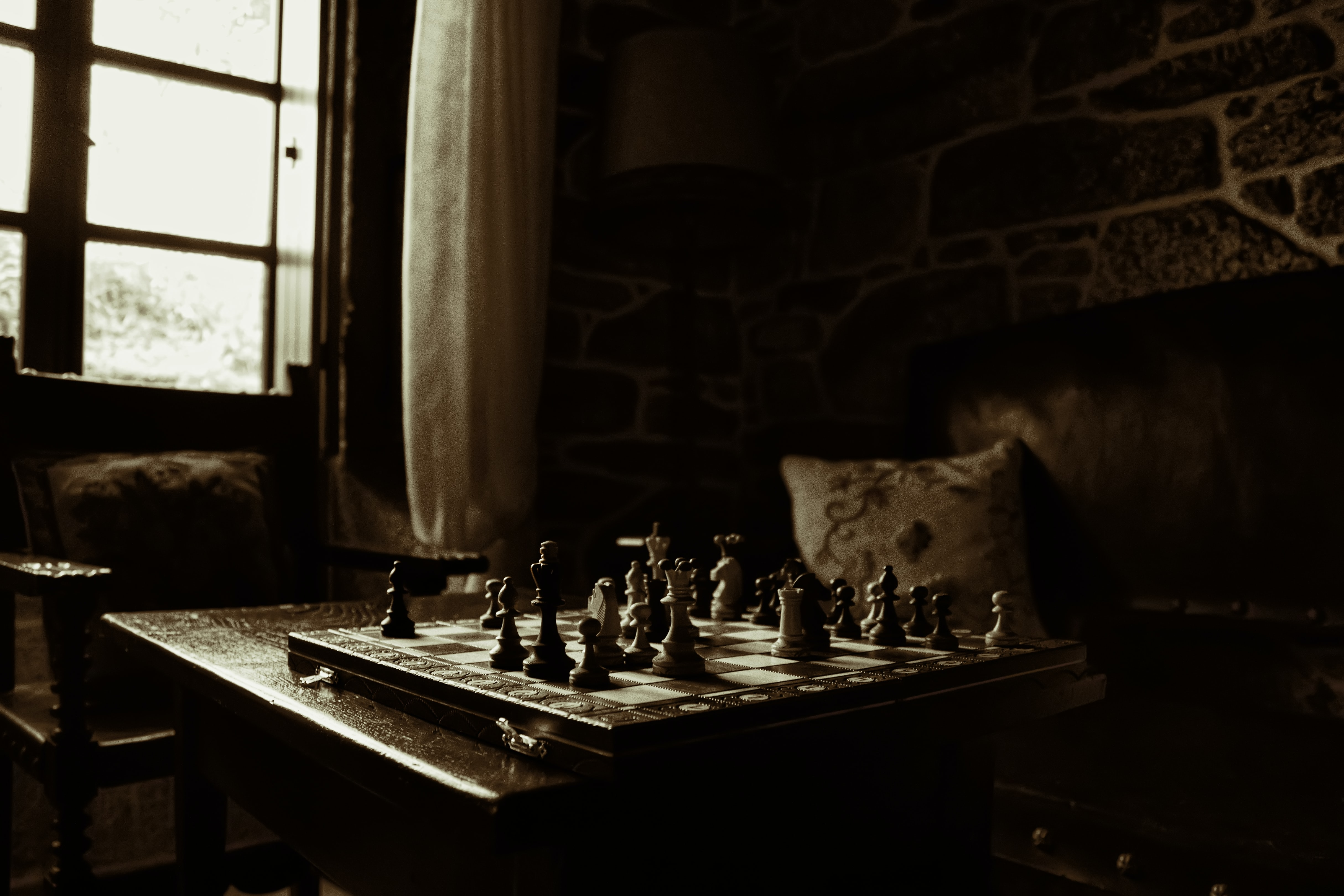 Chess pieces on a board in a dark room