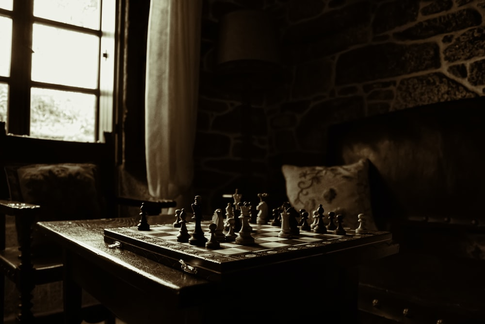 chessboard on table beside window