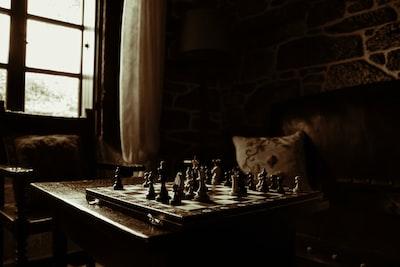 chessboard on table beside window