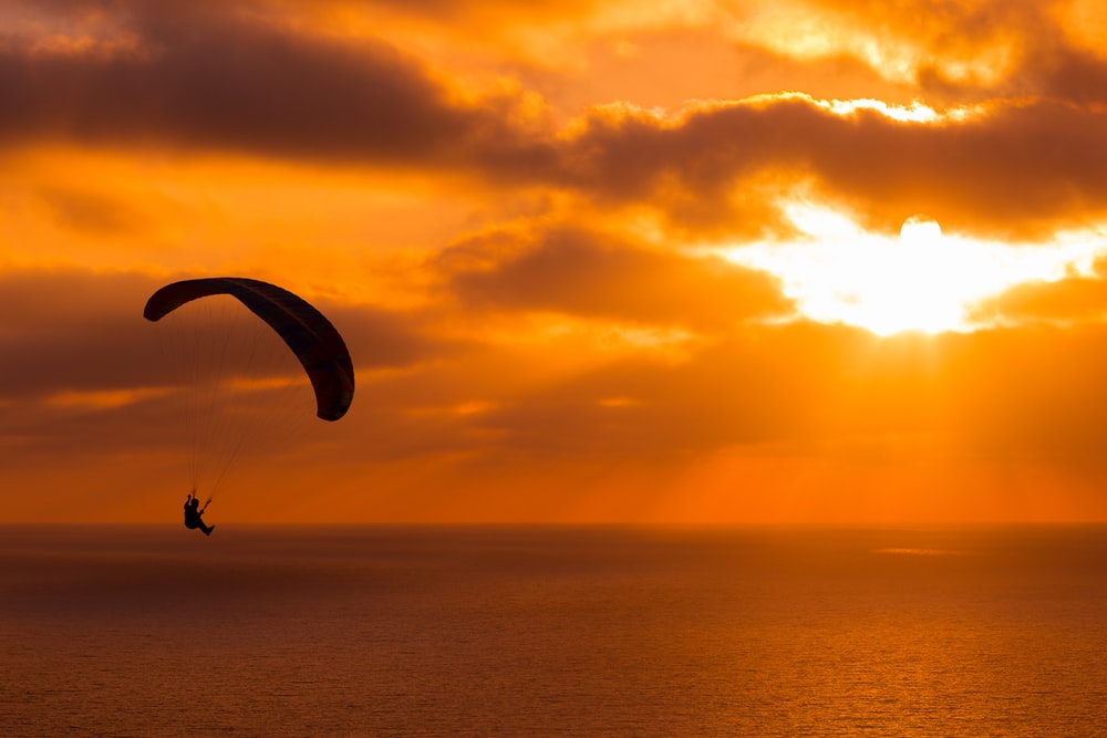 silhouette of person paragliding over ocean