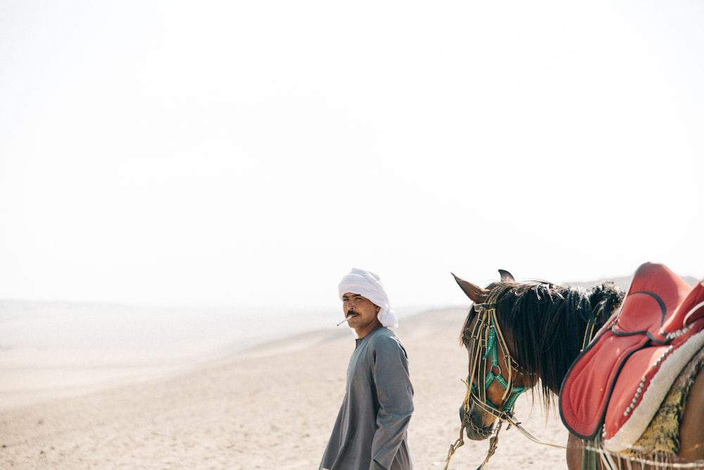 man walking with horse in desert