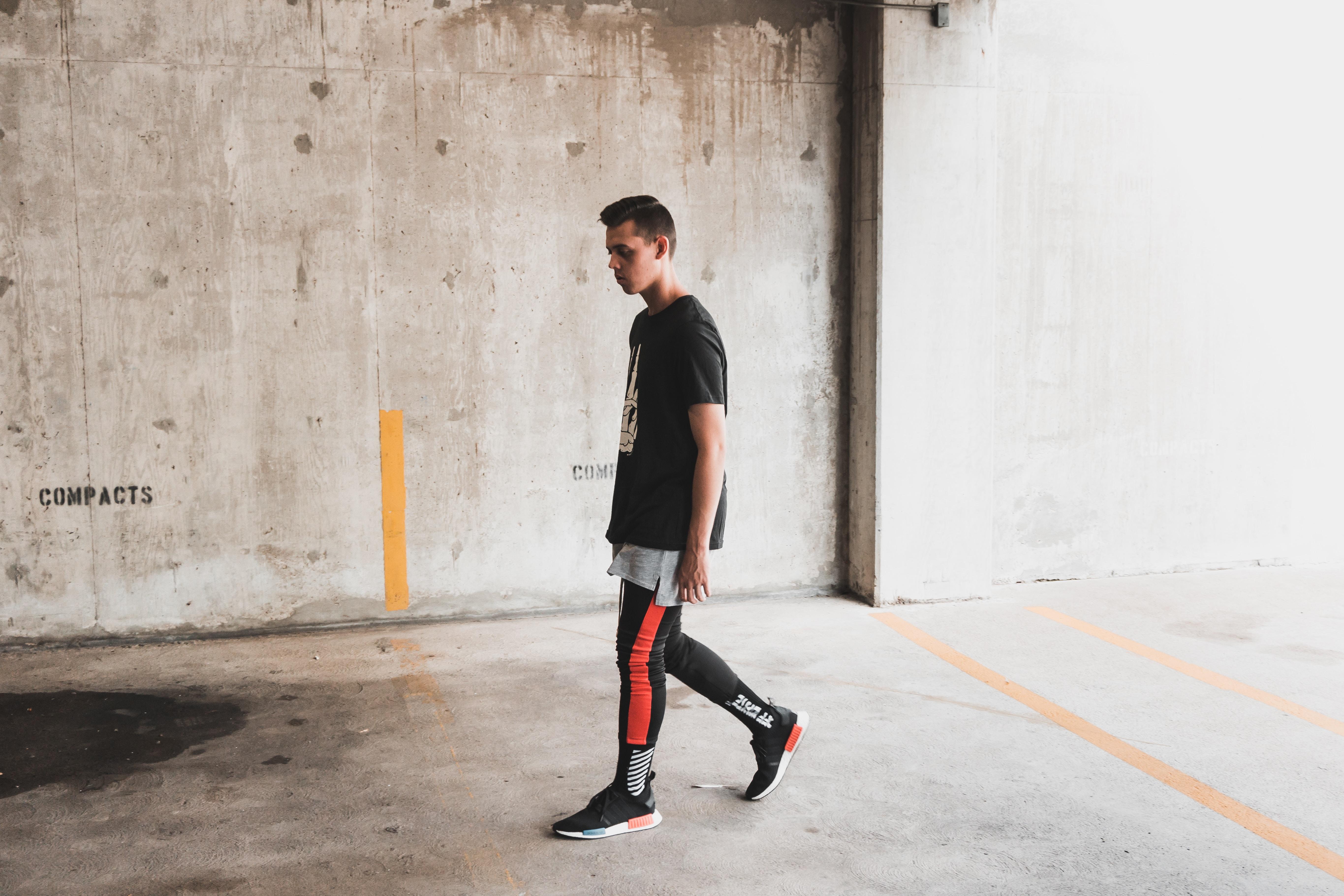 man walking on gray concrete floor