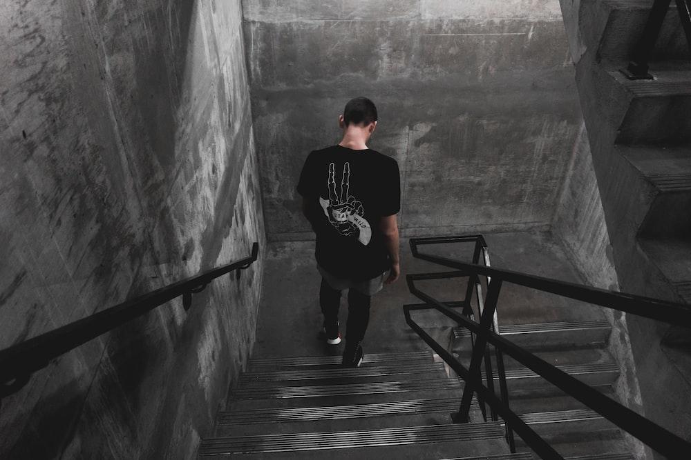 man wearing black shirt walking down the stairs