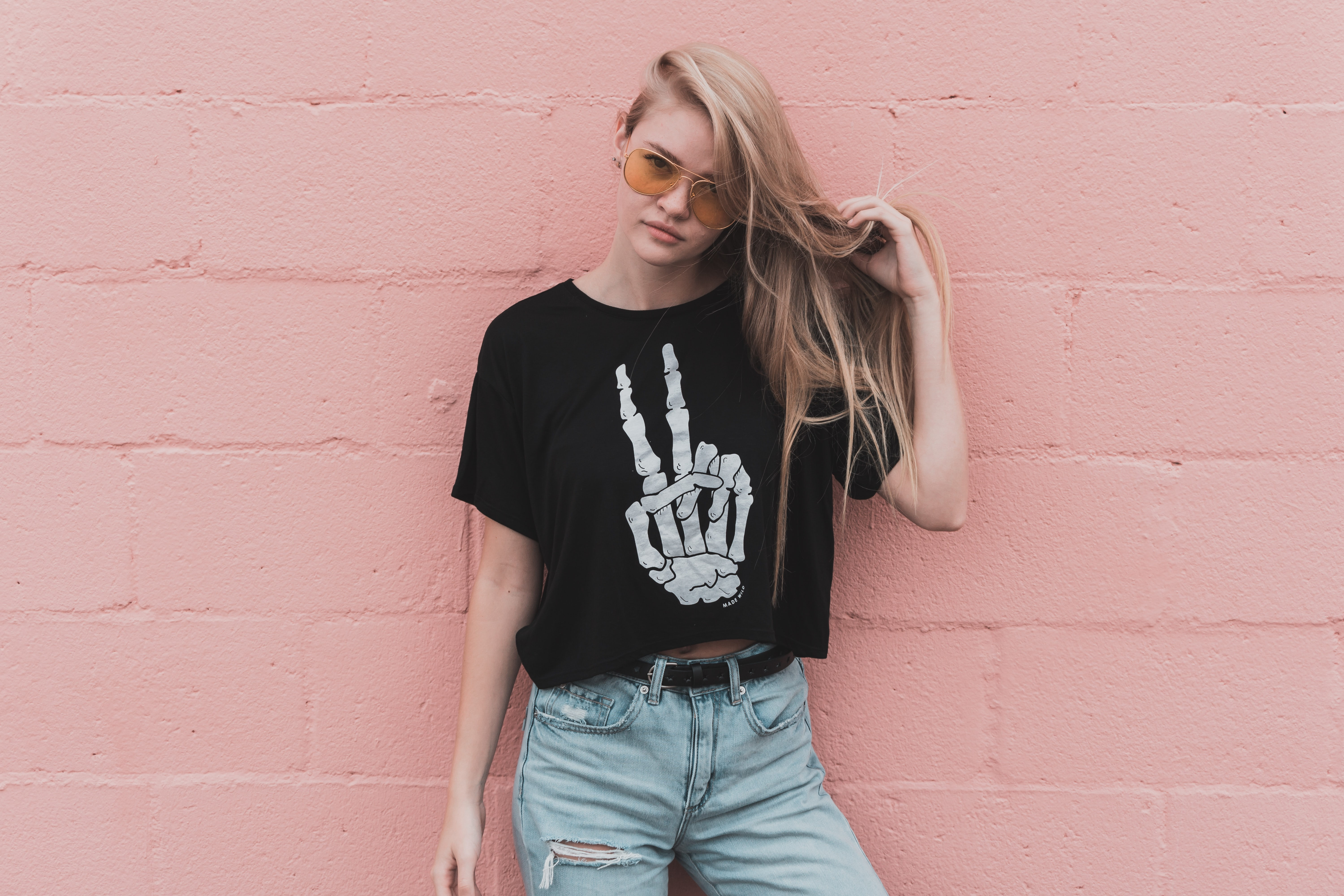 Trendy young woman in a skeleton shirt by a pink wall