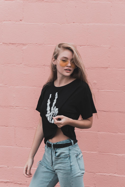 woman standing beside pink wall