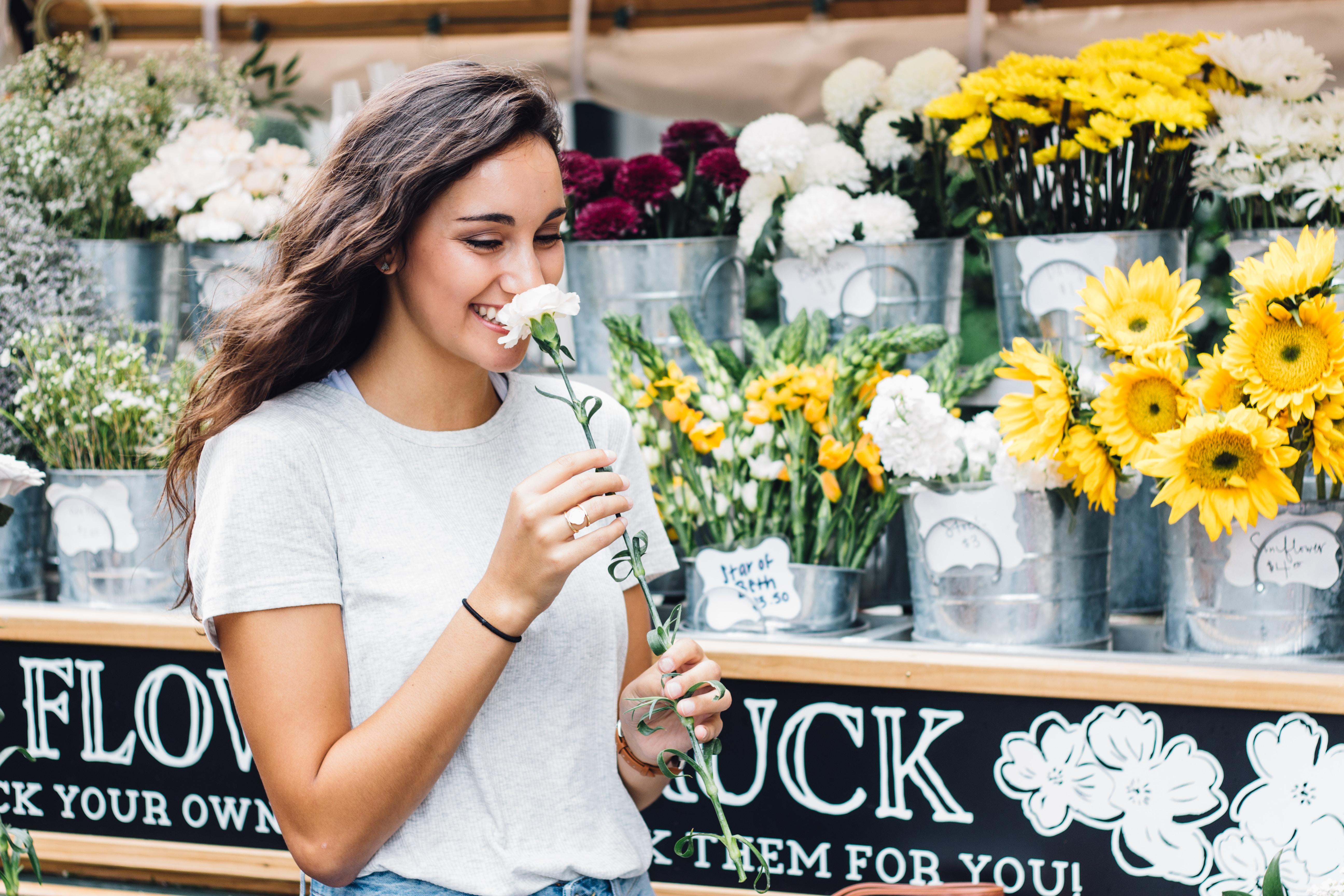 woman smelling flowers beside a flower shop