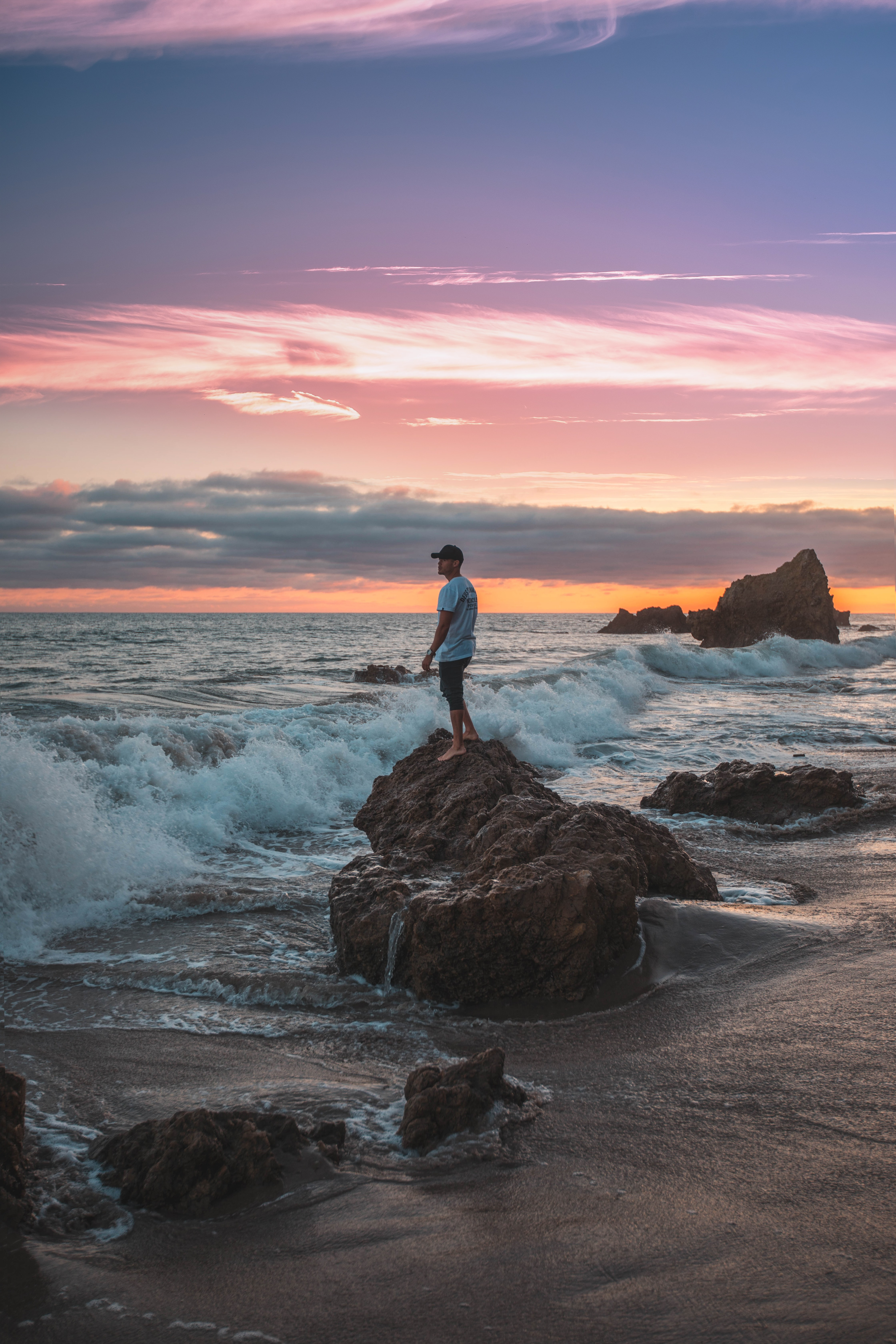 man standing on rock with waves during daytime