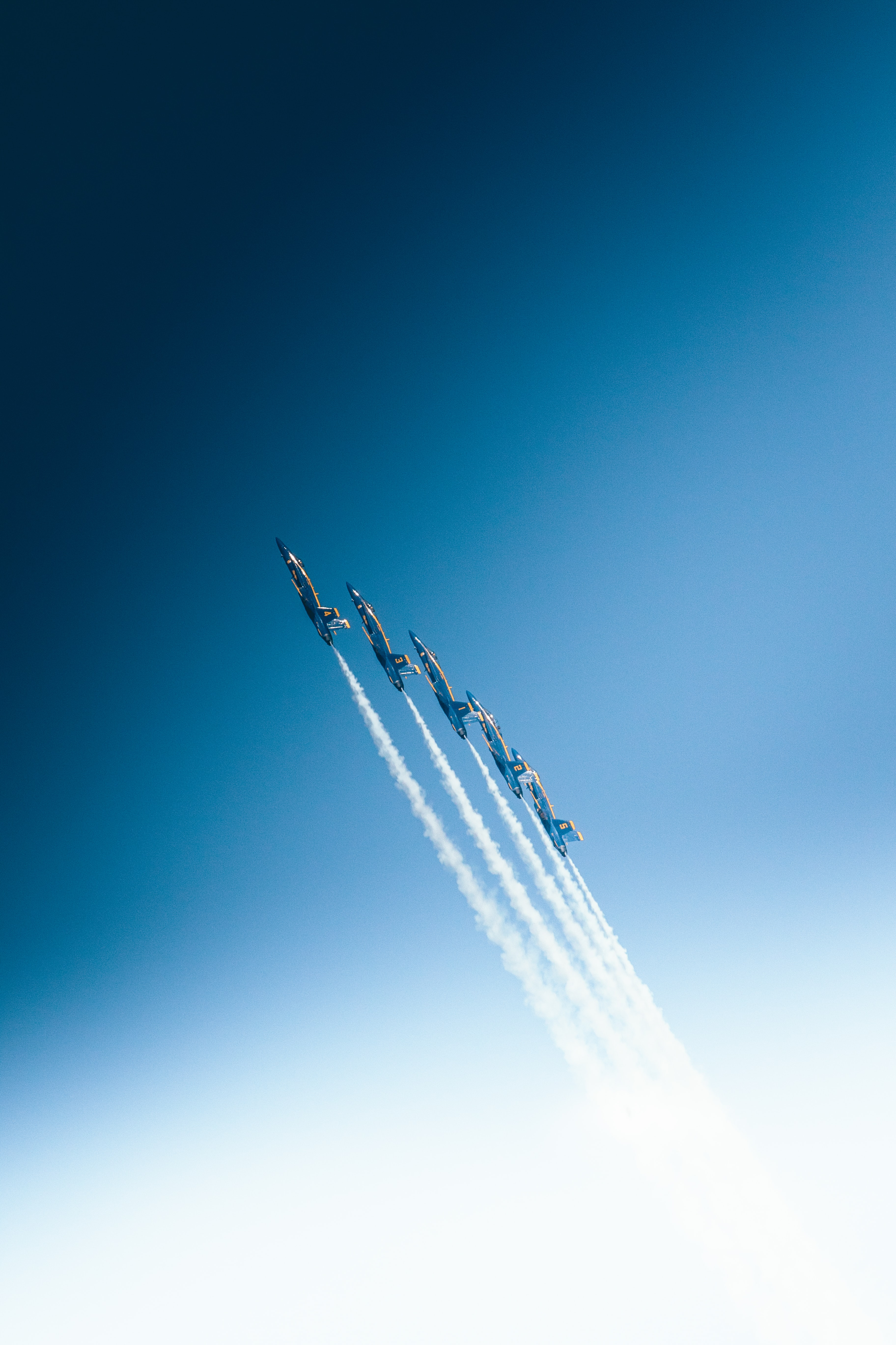 Five aerobatics airplanes with smoke trails in an aerobatics show.