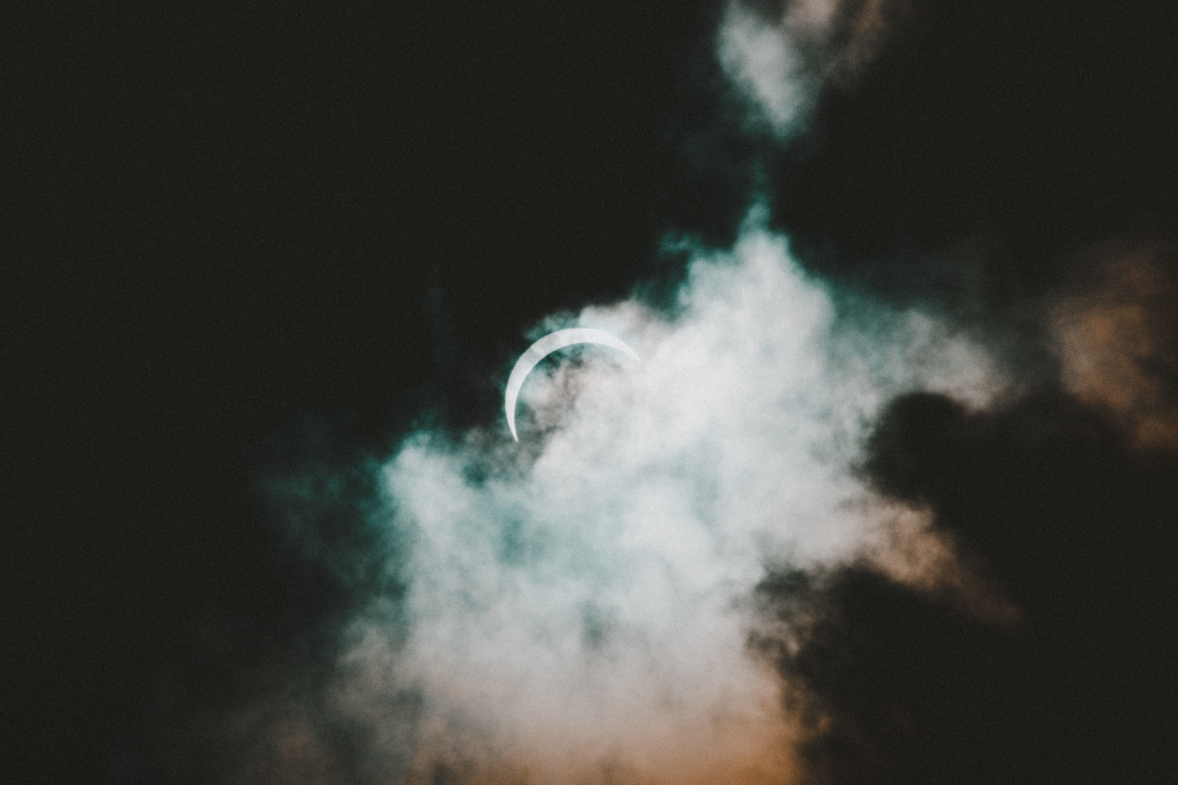 half moon hiding behind white and black clouds