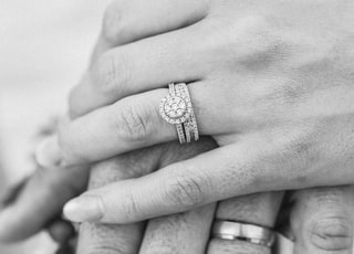 grayscale photo of two hands with rings