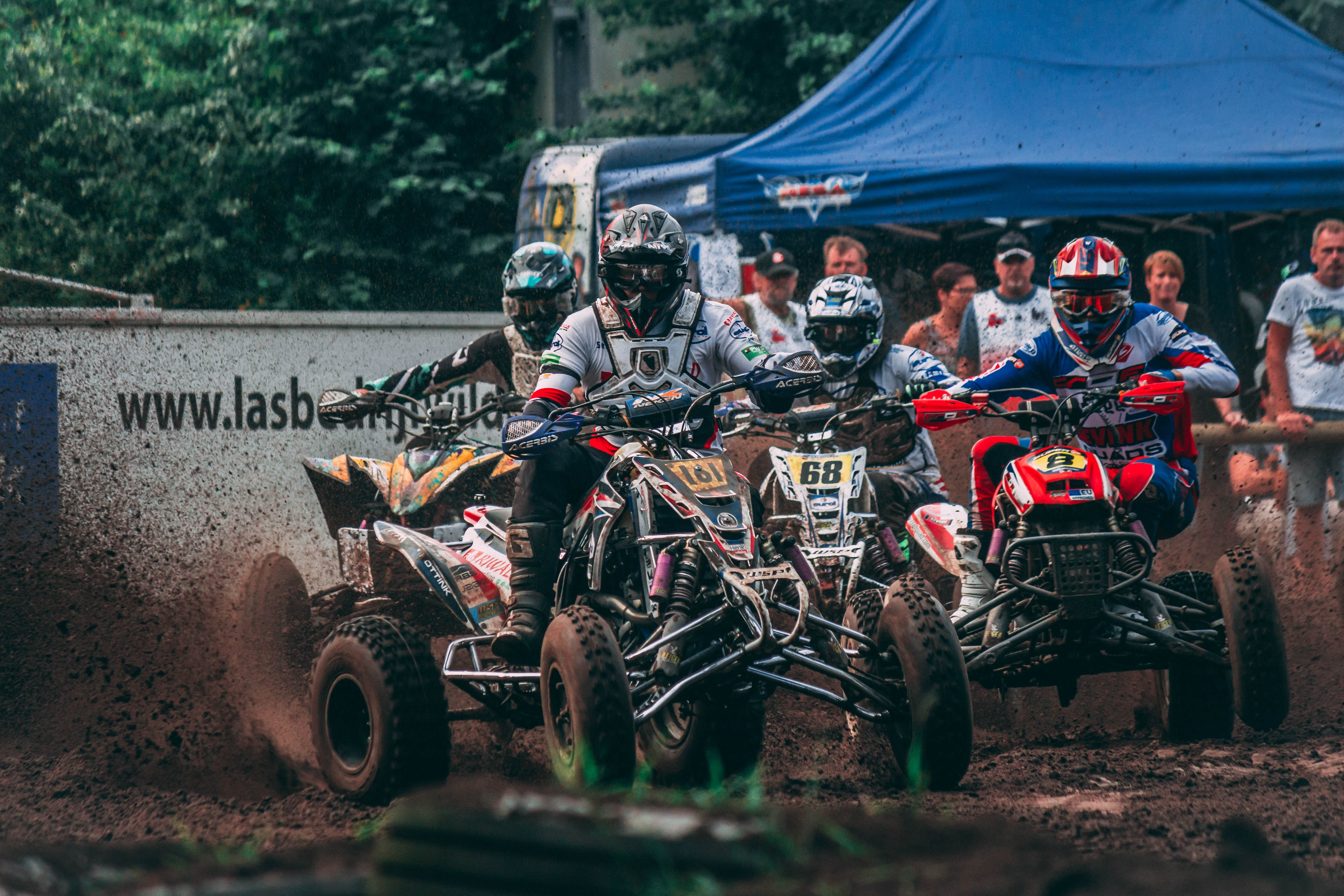four men riding ATVs racing on mud with people watching during daytime