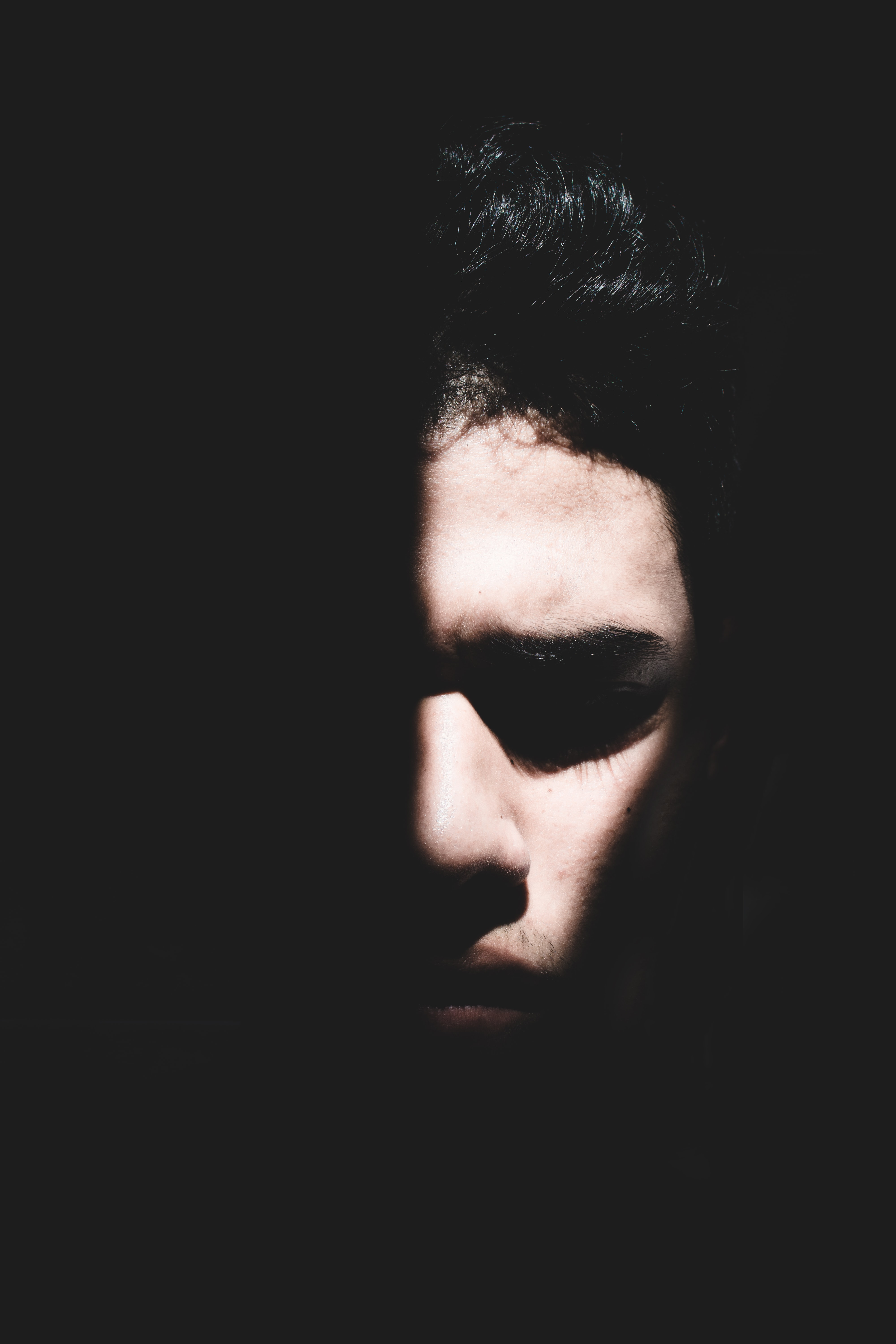 Pensive young man with half his face in light and half in the shadows