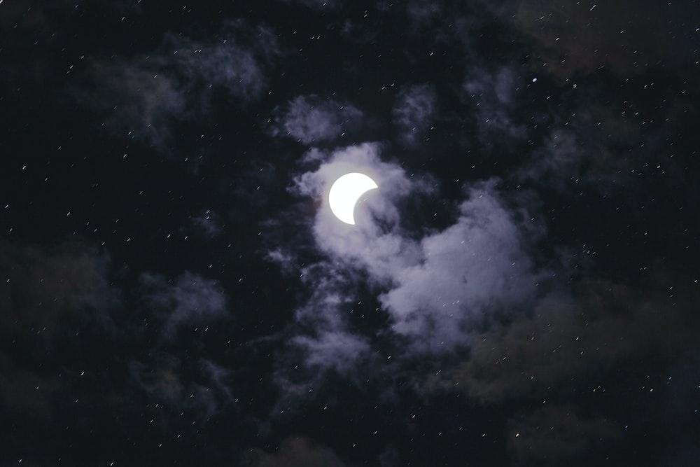 full moon hiding on a cloud