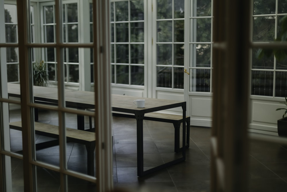 brown wooden table beside glass paneled wall