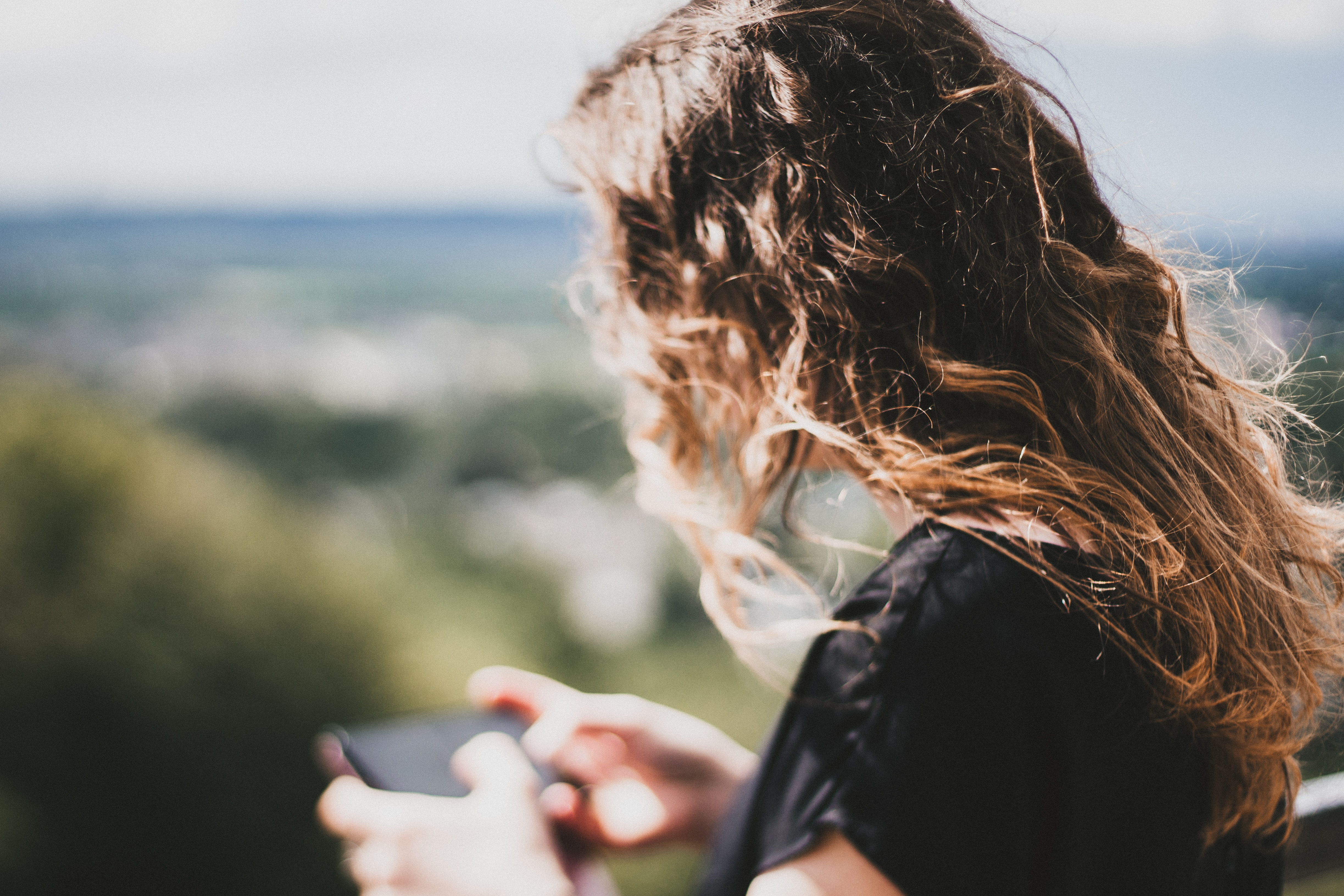 A woman with brown curly hair looks down to use her cell phone outdoors