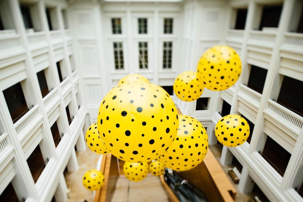 yellow and black polka-dots balloon floating