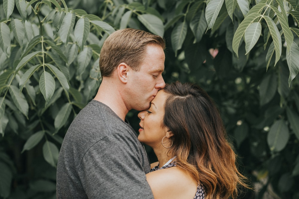 couple hugging near tree leafs