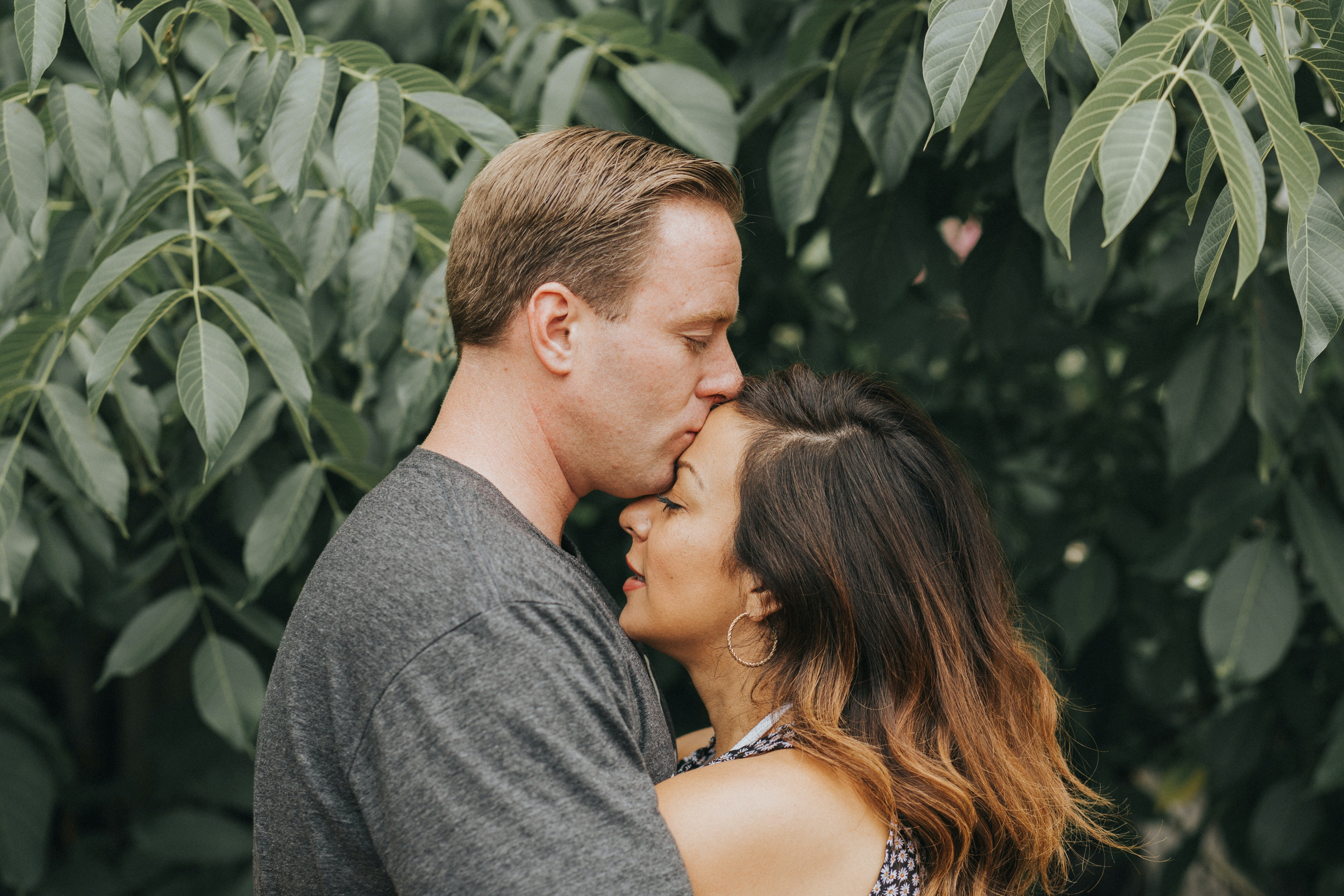 Couple in love hugging and kissing each other on the forehead