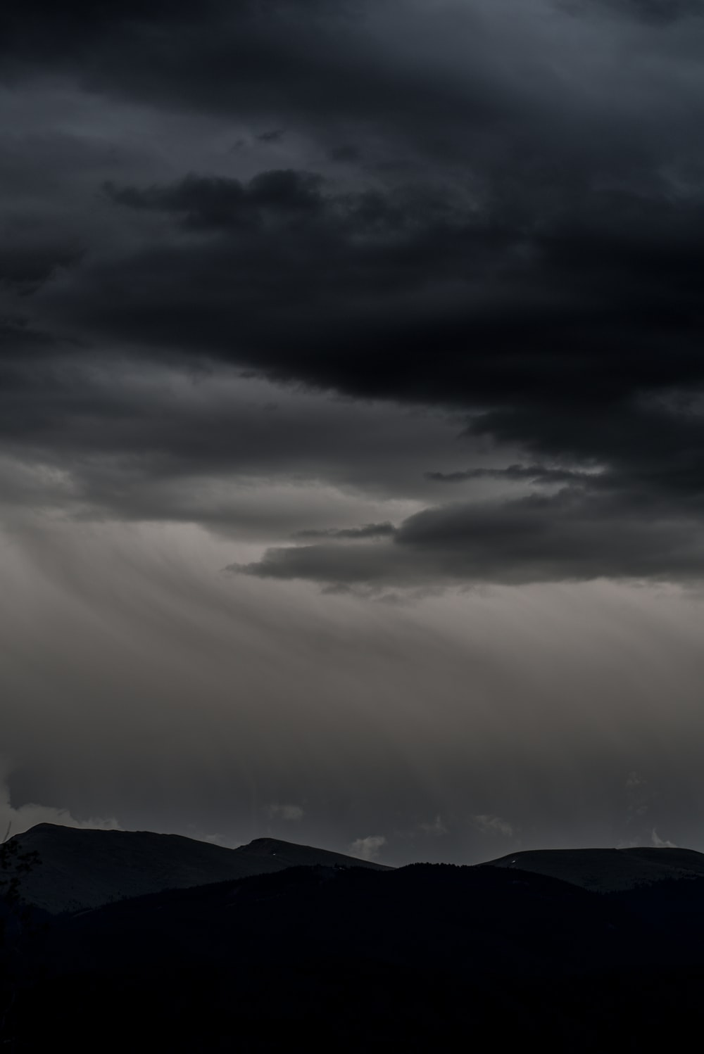 silhouette of mountain under dramatic sky
