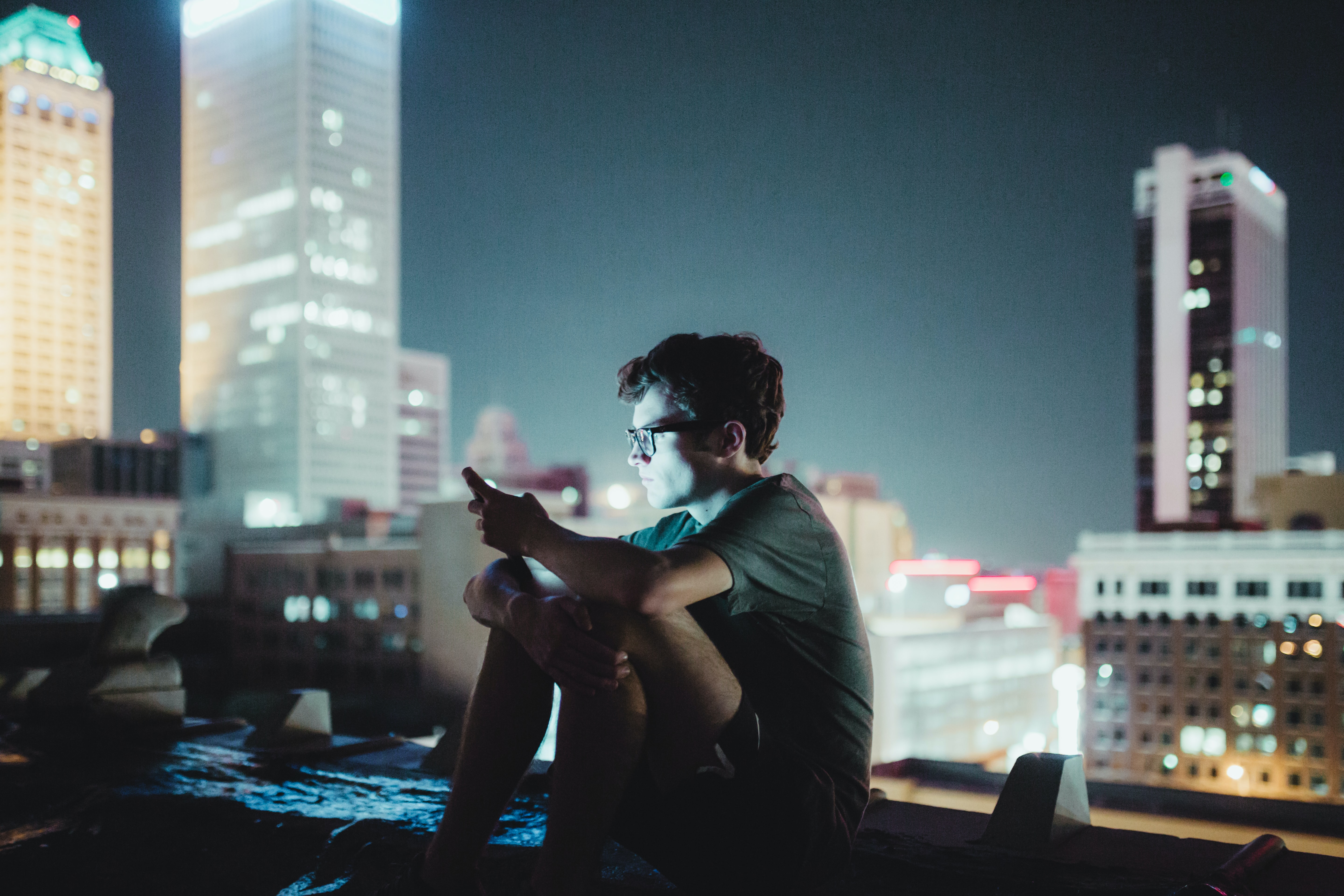 Man sitting alone on a city rooftop staring at his smartphone