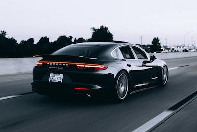 running black porsche sedan porsche zoom background