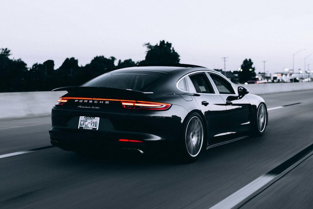 running black Porsche sedan