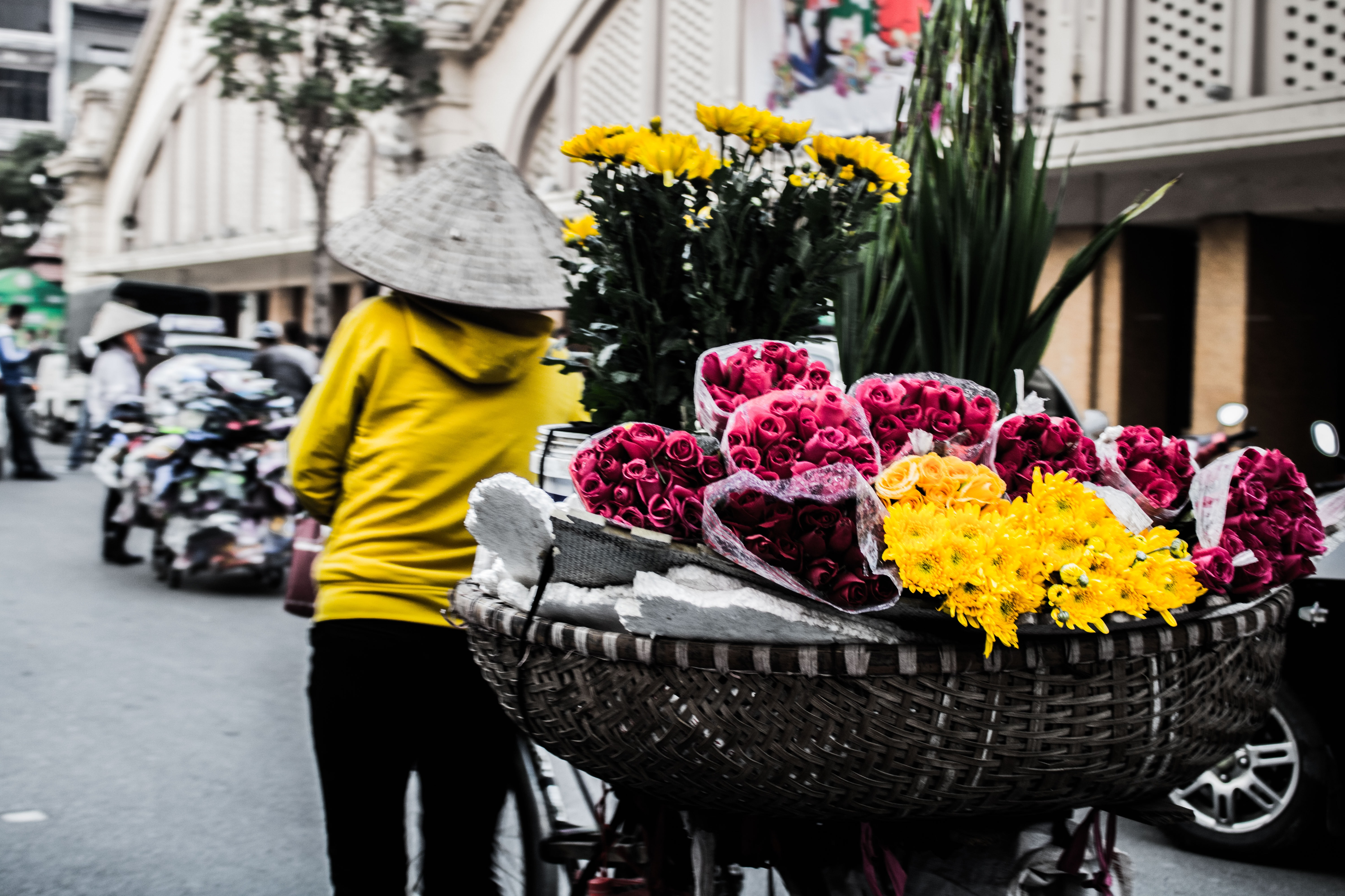 A woman pulling a cart full of flowers.