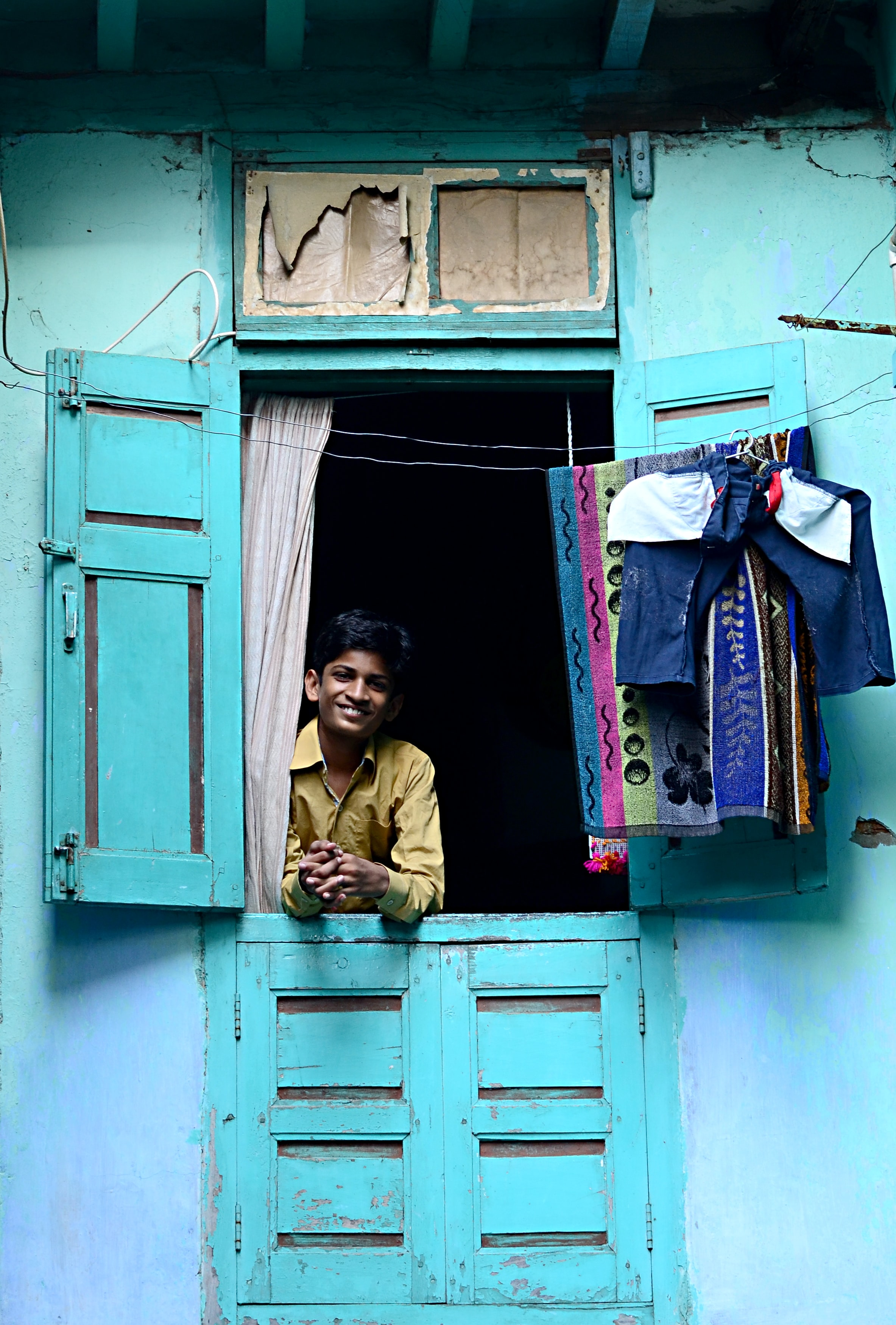 A smiling man leans out an open window in a bright turquoise house in Ahmedabad