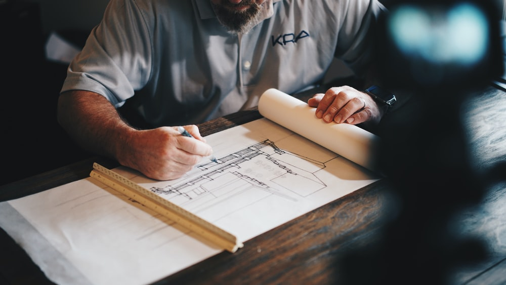 An architect working on a draft with a pencil and ruler