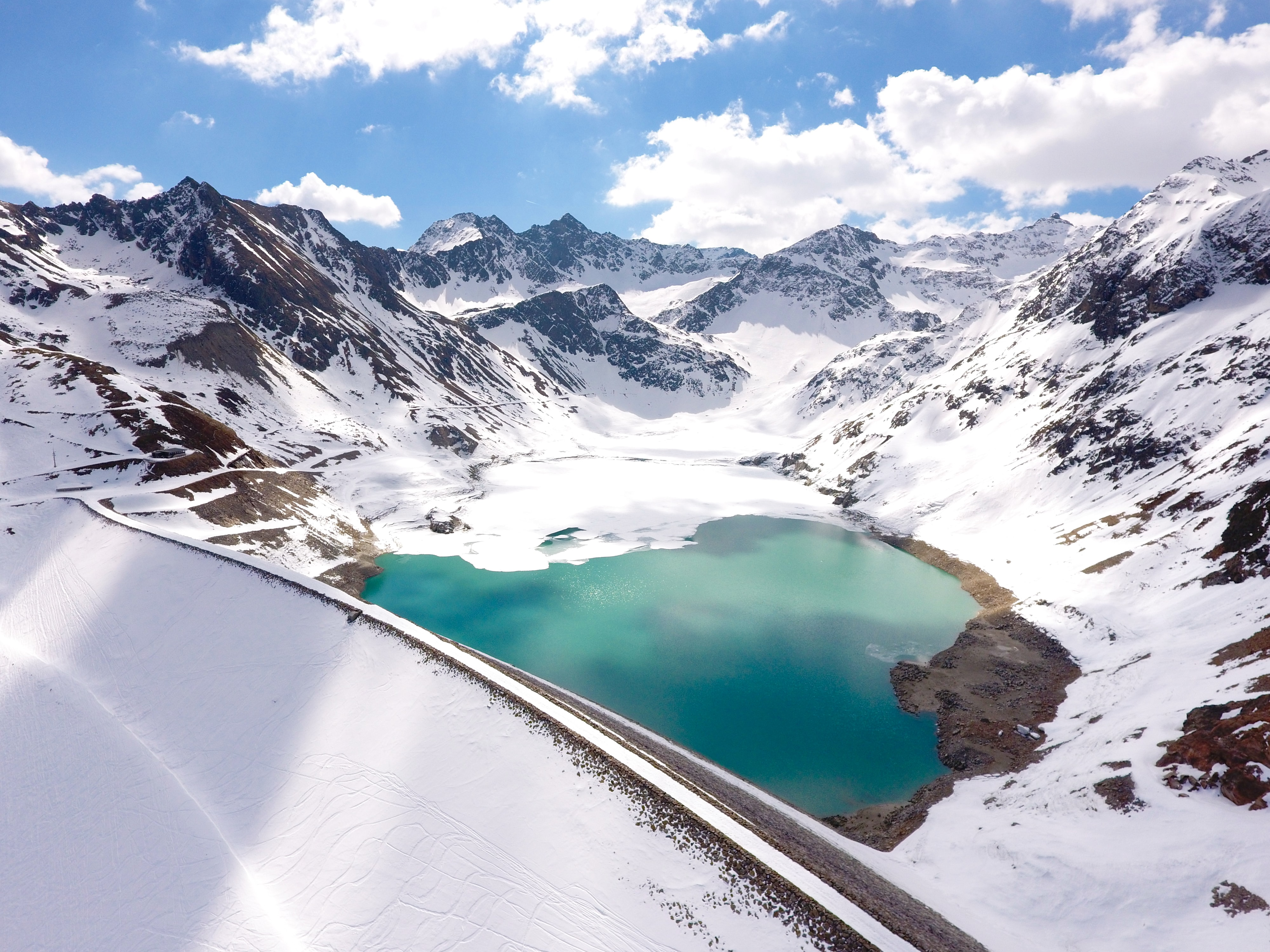 Snowy mountains surround a green lake on a sunny day