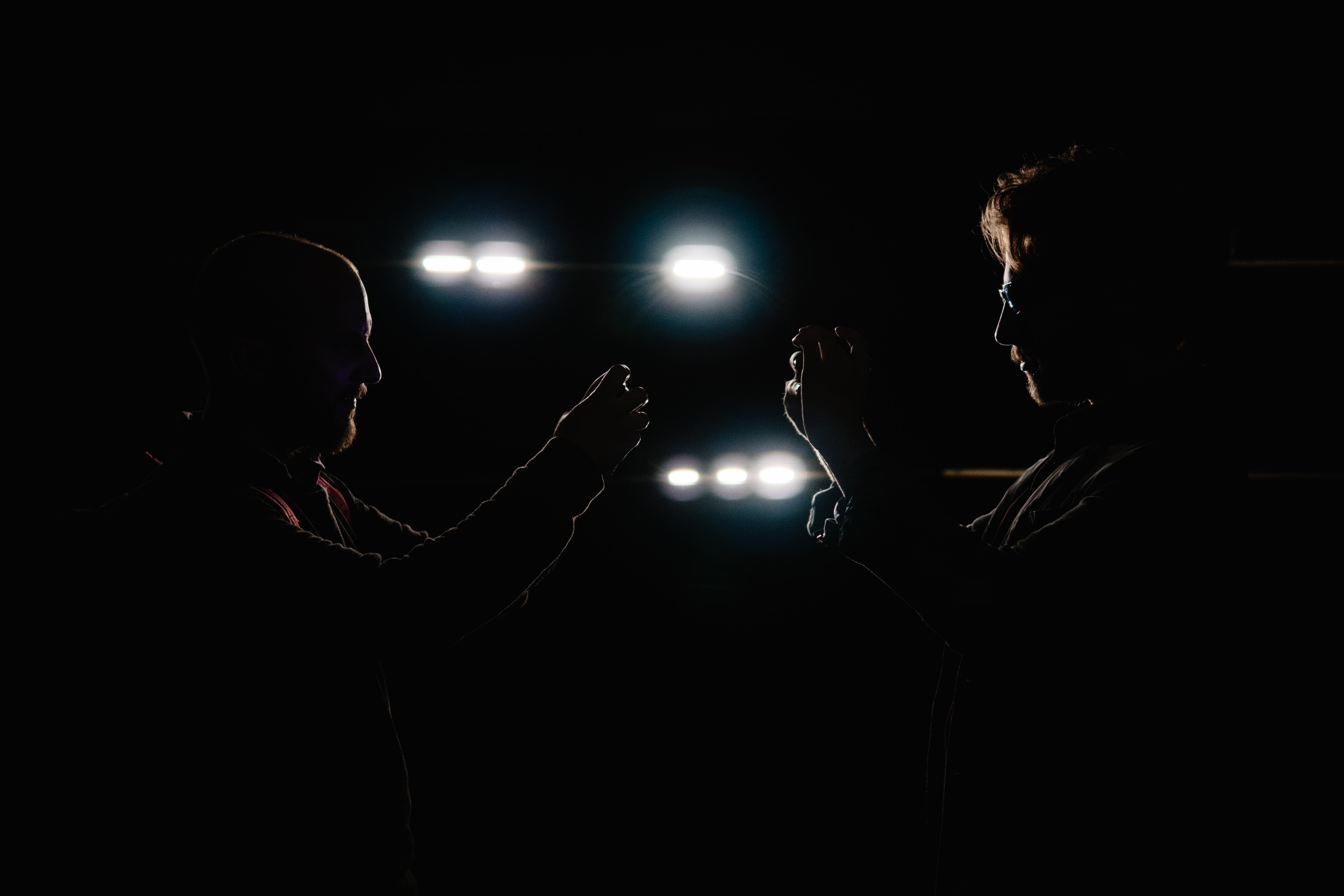 Silhouette of two men facing each other taking a picture in the dark