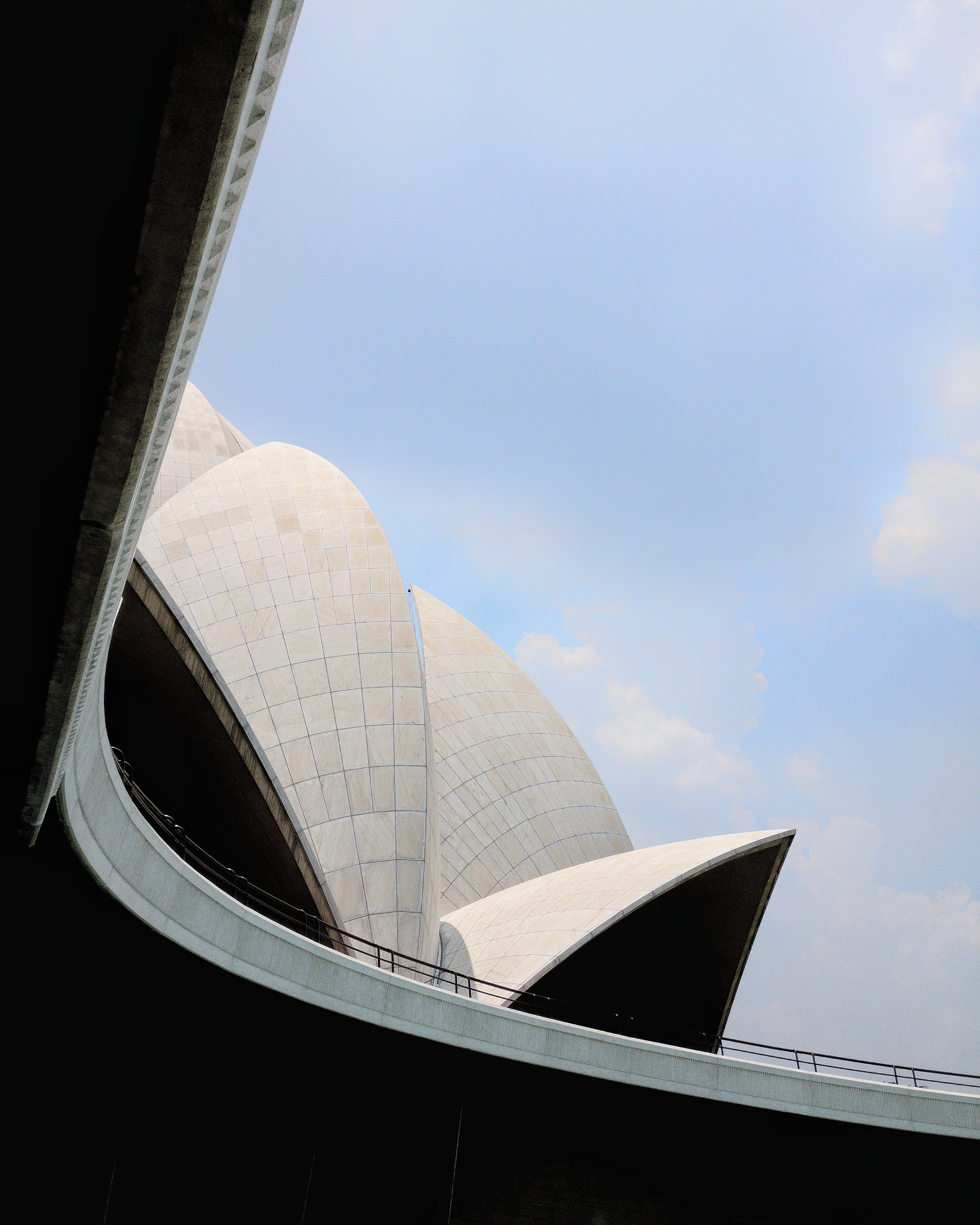 The shell-like facade of Lotus Temple in New Delhi against a pale blue sky