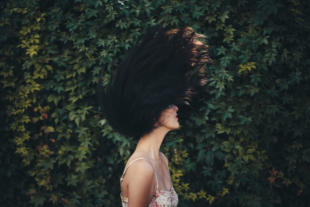 woman waving her hair in front of green leafed wall