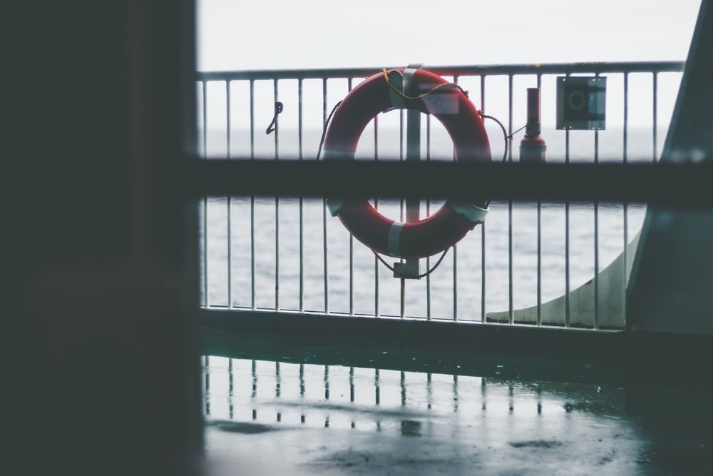 lifesaver ring on gray boat hand rail