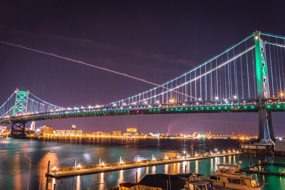 suspension bridge with string lights at nighttime